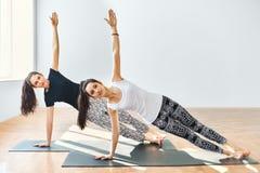 Two young women doing yoga asana side plank Stock Photos