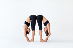 Two young women doing yoga asana standing forward bend pose. Ardha uttanasana royalty free stock photo