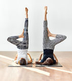 Two young women doing yoga asana supported shoulderstand Royalty Free Stock Image