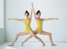 Two young women doing yoga asana Warrior II Pose Stock Photo