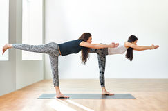 Two young women doing yoga asana Warrior III Pose Stock Photos