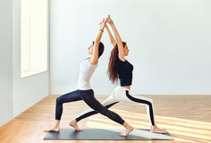 Two young women doing yoga asana warrior one pose Stock Photography