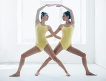 Two young women doing yoga asana warrior pose variation Royalty Free Stock Photography