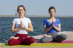 Two young women doing yoga at nature. Fitness, sport, yoga and healthy lifestyle concept - group of people making yoga pose on stock image