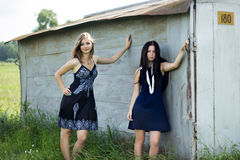 Two young women in dresses standing next to the garage Royalty Free Stock Photography