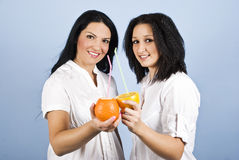 Two young women drinking citrus juice Royalty Free Stock Image