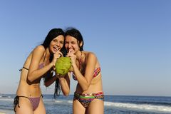 Two Young Women Drinking Coconut Water Stock Image