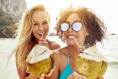 Two young women drinking from coconuts on a tropical beach stock photos