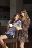 Two young women drinking coffee at a bar Stock Images
