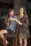 Two young women drinking coffee at a bar Royalty Free Stock Photo