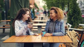 Two young women are drinking coffee and talking sitting at table in outdoor cafe in park, young women are having fun and. Two pretty young women are drinking stock video footage