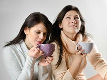 Two   young women drinking tea Stock Photos