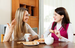Two young women drinking tea with cookies Royalty Free Stock Photos