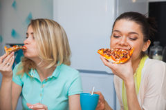 Two young women eat pizza. Girls taste italian traditional food Royalty Free Stock Photography