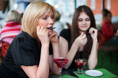 Two young women eating a dessert Stock Images