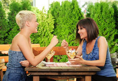 Two young women eating fruit salad Stock Photography