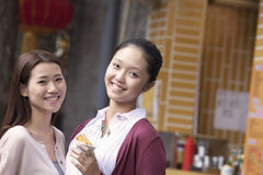 Two Young Women Eating Snacks Stock Photography