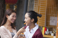Two Young Women Eating Snacks Stock Photo