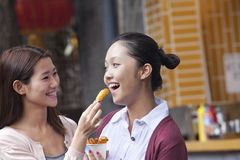 Two Young Women Eating Snacks Royalty Free Stock Image