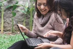 Bestfriend daily activity. Two young women enjoy playing laptop by sitting near the tent in the backyard Royalty Free Stock Photography