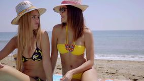 Two young women enjoying a day at the beach. Two attractive young women enjoying a day at the beach together sitting on a towel in the sand chatting in their stock video