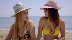 Two young women enjoying a day at the beach stock video