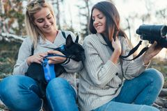 Two young women enjoying in forest hiking with their dog royalty free stock photos