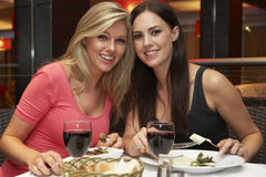 Two Young Women Enjoying Meal In Restaurant Royalty Free Stock Image