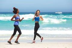 Two young women enjoying a run on the beach Stock Image