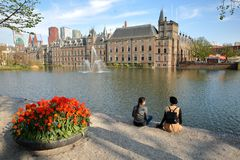 Two young women enjoying a sunny day along the Hofvijver lake with the Binnenhof in the background and colorful tulips. THE HAGUE, NETHERLANDS - APRIL 18, 2019 stock photo