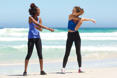 Two young women enjoying workout exercise at the beach Stock Image