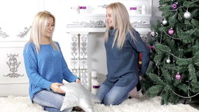 Two young women exchanging Christmas presents. Two young, blond hair, women woman, lady, ladies exchanging giving each other Christmas presents, gifts. Smiling stock video footage