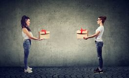 Two women exchanging with gift boxes looking happily at each other royalty free stock images