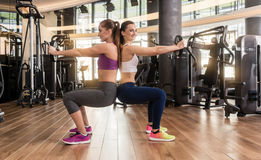 Two young women exercising together back to back with weight pla. Side view of two young women smiling while exercising together back to back with weight plates Stock Images