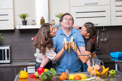Two young women are fed bananas midle age man Royalty Free Stock Image