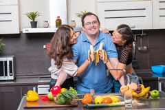 Two young women are fed bananas midle age man Stock Image