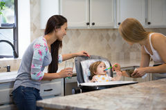 Two young women feeding little girl in highchair. Royalty Free Stock Photo