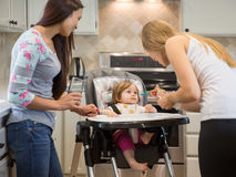 Two young women feeding little girl in highchair. Royalty Free Stock Image