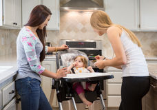Two young women feeding little girl in highchair. Royalty Free Stock Photos