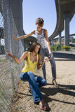 Two young women by fence beneath overpass, looking at mobile phone, smiling Stock Photography