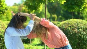 Two young women fighting pulling hairs of each other, female conflict, quarrel. Stock footage stock footage