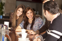 Two young women flirting at a bar. Two beautiful young women with great teeth enjoying their lunch break, sitting at a bar, flirting, drinking coffee, smiling stock photos