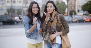 Two young women flirting with the camera. Two gorgeous trendy young women flirting with the camera blowing kisses off the palms of their hands  urban street stock video footage