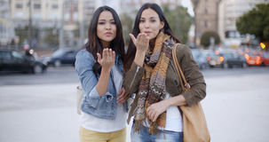 Two young women flirting with the camera. Two gorgeous trendy young women flirting with the camera blowing kisses off the palms of their hands urban street royalty free stock photography