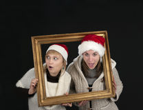 Two young women in a frame, on black Royalty Free Stock Photo