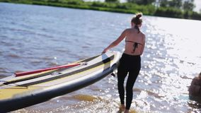 Two young women friends carry sup board to river to start floating on sunny day. Two young pretty women friends wearing swimming suit carry big stand up paddle stock video