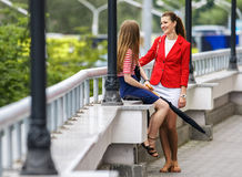 Two young women friends chatting in city Stock Images