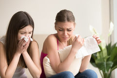 Two young women friends crying together at home. Two funny young women crying, wiping tears, blowing noses with handkerchiefs while sitting at home. Female Royalty Free Stock Images