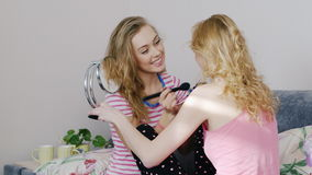 Two young women friends doing make-up at home in the bedroom. Friends at the pajama party stock video