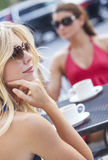 Two Young Women Friends Drinking Coffee in Cafe. Two beautiful and sophisticated young women friends wearing sunglasses and drinking coffee around a modern city Stock Images